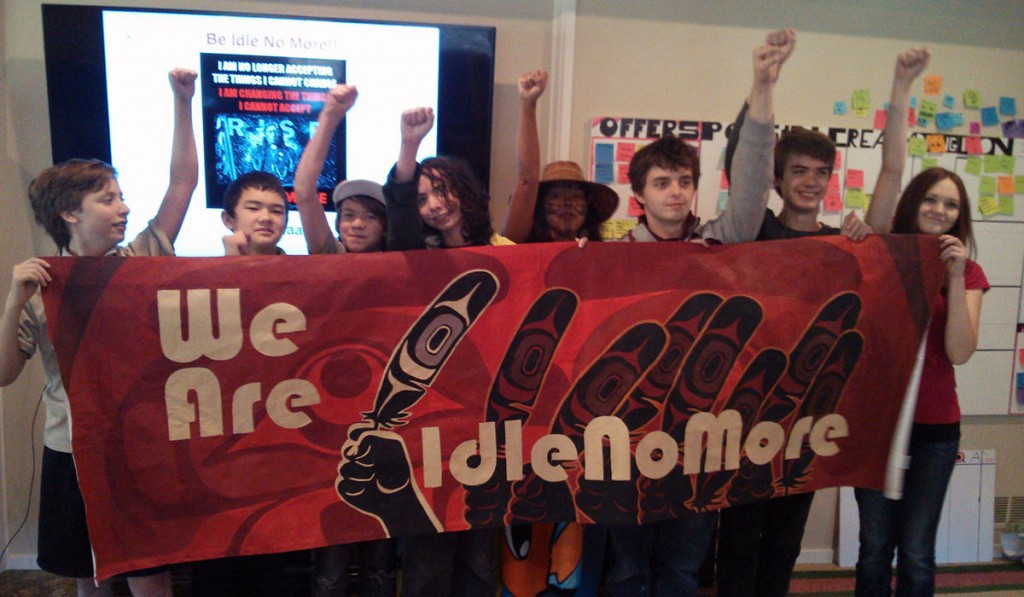 The kids posing with Sweetwater's Idle No More banner.